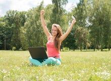 Glückliche Internet-Einkaufsfrau online mit dem Laptop- und Kreditkartesitzen im Freien auf grünem Gras Kaufende Sachen des Inter Stockfotografie