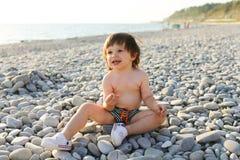 Glückliche 2 Jahre Junge auf den Kieseln setzen auf den Strand Stockbilder