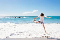 Glückliche 7 Jahre Junge, die auf den Strand springen Lizenzfreies Stockfoto