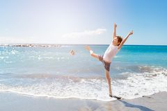 Glückliche 7 Jahre Junge, die auf den Strand springen Lizenzfreie Stockfotos