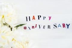Glückliche Jahrestags-Buchstaben herausgeschnitten von den Zeitschriften und von weißem Peoni lizenzfreie stockfotografie