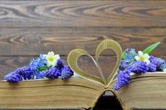 Glückliche Jahrestagskarte mit Blumen und Herz formten Buchseiten Stockbild