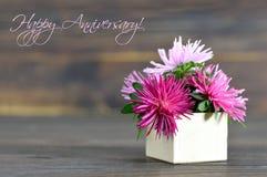 Glückliche Jahrestagskarte mit Blumen vereinbarte in der Geschenkbox Stockfoto