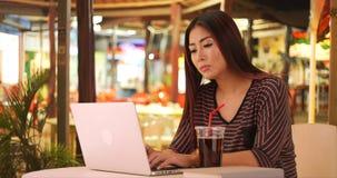 Glückliche japanische Frau, die Computertelefon verwendet stockfotos