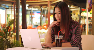 Glückliche japanische Frau, die Laptoptelefon verwendet stockfotos