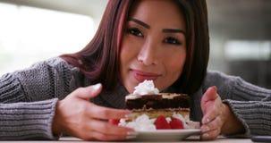 Glückliche japanische Frau, die zu Hause Kuchen isst lizenzfreies stockbild