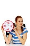 Glückliche Jugendfrau, die Bürouhr hält Stockfotos