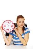 Glückliche Jugendfrau, die Bürouhr hält Lizenzfreies Stockfoto