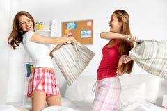 Glückliche jugendlich Freundinnen, die zu Hause Kissen kämpfen stockbilder