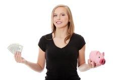 Glückliche jugendlich Holding eine piggy Querneigung und Dollar Stockbilder