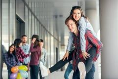 Glückliche jugendlich Mädchen und die Jungen, die guten Spaß haben, setzen draußen Zeit fest Lizenzfreies Stockbild