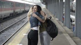 Glückliche jugendlich Mädchen vereinigten sich in der Bahnstation wieder nach Hause, die Hand in Hand umarmt und geht stock video