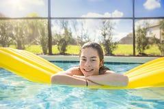 Glückliche Jugendliche, die in einen Swimmingpool im Freien schwimmt lizenzfreies stockfoto