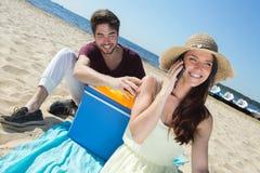 Glückliche Jugendliche, die ihre Freunde beim Genießen des Strandes anrufen Stockfotografie