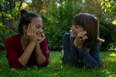 Glückliche Jugendliche, die im Gras am Park in Verbindung stehen stockfotografie