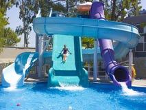 Glückliche Jugendliche, die unten durch Wasserrutsche in das Pool geht lizenzfreie stockbilder