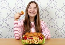 Glückliche Jugendliche mit Hühnernuggets und Pommes-Frites lizenzfreie stockfotografie