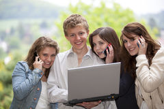 Glückliche Jugendliche mit Mobiltelefonen und einem Laptop Stockbild