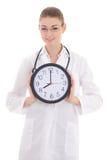 Glückliche junge Ärztin, die Bürouhr lokalisiert auf Weiß hält Stockfotos
