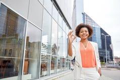 Glückliche junge Afroamerikanergeschäftsfrau in der Stadt stockbilder