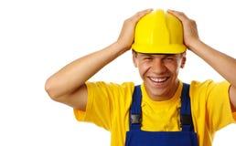Glückliche junge Arbeitskraft setzte seine Hände auf harten Hut Stockbild
