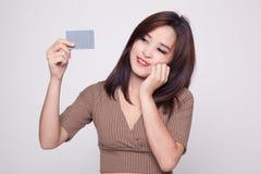 Glückliche junge Asiatin mit einer leeren Karte lizenzfreie stockfotografie