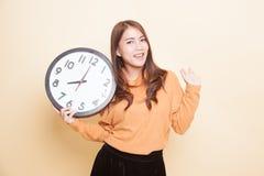 Glückliche junge Asiatin mit einer Uhr lizenzfreie stockfotos