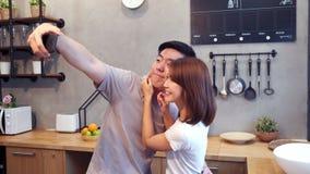 Glückliche junge asiatische Paare unter Verwendung des Smartphone für selfie beim in der Küche zu Hause kochen stock video