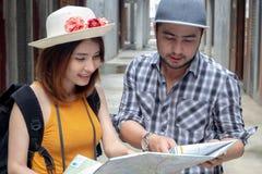 Glückliche junge asiatische Paare, welche die Karte schaut Richtung auf Flitterwochenferien halten Touristische Leute auf Sommer  lizenzfreie stockbilder