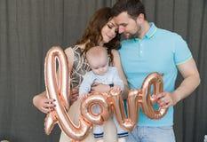 Glückliche junge attraktive Familie mit Baby Stockfotografie