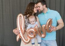 Glückliche junge attraktive Familie mit Baby Stockbilder