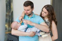 Glückliche junge attraktive Familie mit Baby Lizenzfreies Stockbild