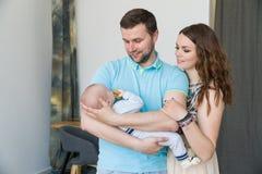 Glückliche junge attraktive Familie mit Baby Lizenzfreie Stockfotos