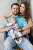 Glückliche junge attraktive Familie mit Baby Lizenzfreie Stockfotografie