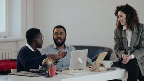 Glückliche junge attraktive kaukasische ManagerGeschäftsfrau, die mit zwei schwarzen männlichen Kollegen am modernen Bürotisch sp stock video