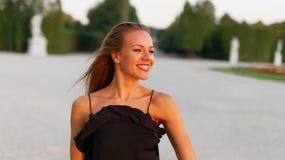Glückliche junge ausgeglichene Frauenzähne lächeln im Park, draußen stockbilder