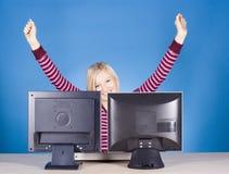Glückliche junge blonde Frau an den zwei Bildschirmen Stockfotos