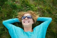 Glückliche junge blonde Frau in der Sonnenbrille, die auf dem Gras liegt Lizenzfreies Stockbild