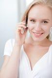 glückliche junge blonde Frau, die über ein Mobiltelefon spricht Lizenzfreies Stockfoto