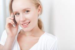 Glückliche junge blonde Frau, die über ein Mobiltelefon spricht Lizenzfreie Stockbilder
