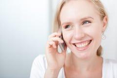Glückliche junge blonde Frau, die über ein Mobiltelefon spricht Stockbilder