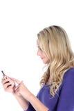 Glückliche junge blonde Frau, die auf einem Handy wählt Lizenzfreies Stockbild
