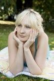 Glückliche junge blonde Frau, die auf ihrem Bauch liegt Stockfotografie