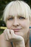Glückliche junge blonde Frau, die auf ihrem Bauch liegt Stockbilder