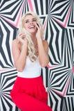 Glückliche junge blonde Frau, die durch Telefon spricht Stockfotografie
