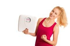 Glückliche junge blonde Frau, die eine Skala zeigt, da sie perfekte Form hat Stockbilder