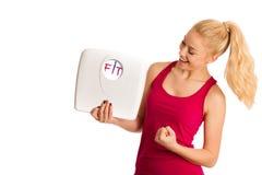 Glückliche junge blonde Frau, die eine Skala zeigt, da sie perfekte Form hat Lizenzfreie Stockfotos