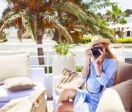 Glückliche junge blonde Frau, die Foto mit Kamera macht Stockbild