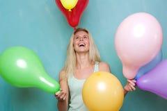 Glückliche junge blonde Frau, die mit Ballonen spielt Lizenzfreie Stockbilder