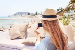 Glückliche junge blonde Frau, die Smartphonefoto mit intelligentem Telefon macht Stockfotos